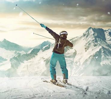Skifahrer im Schnee mit dynamischer Siegerpose
