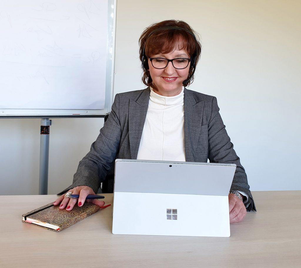 Lucia Gräfe lächelnd am Laptop arbeitend