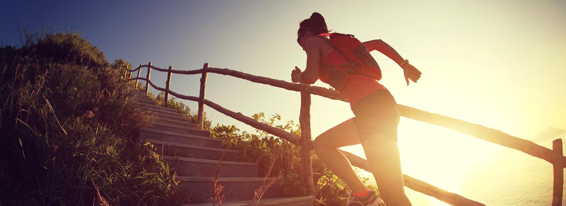 Sportlerin rennt draußen eine Treppe im Sonnenlicht hoch