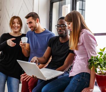 Junge Leute im Büro mit Laptop und Kaffe bei einer Besprechung