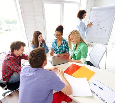 Team bei Workshop am Tisch mit Flipchart
