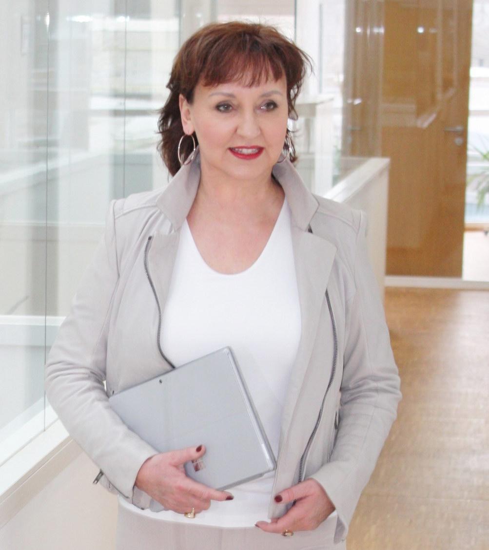 Lucia Gräfe mit Laptop im Bürogebäude auf dem Weg